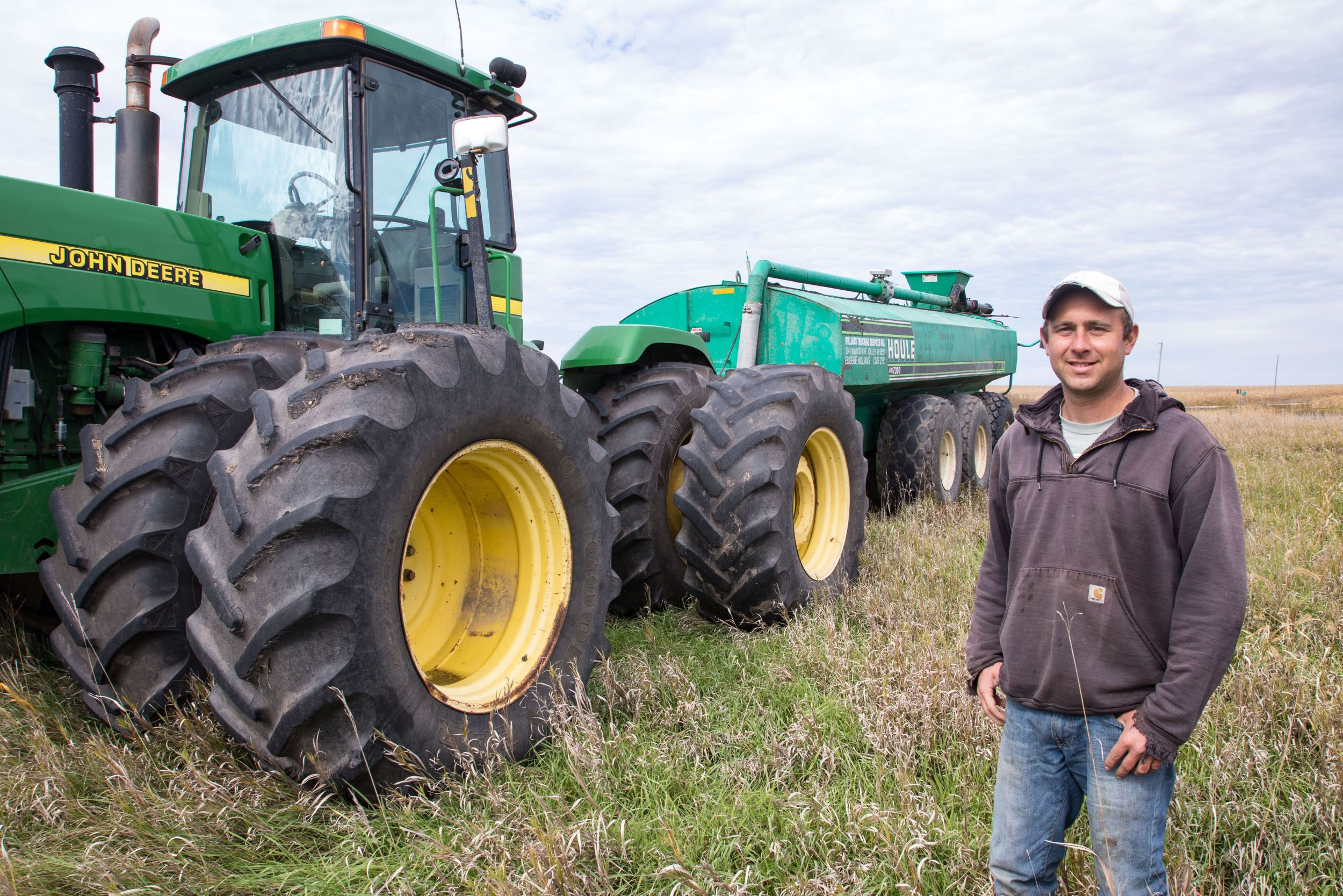 Brandon standing next to his farming equipment